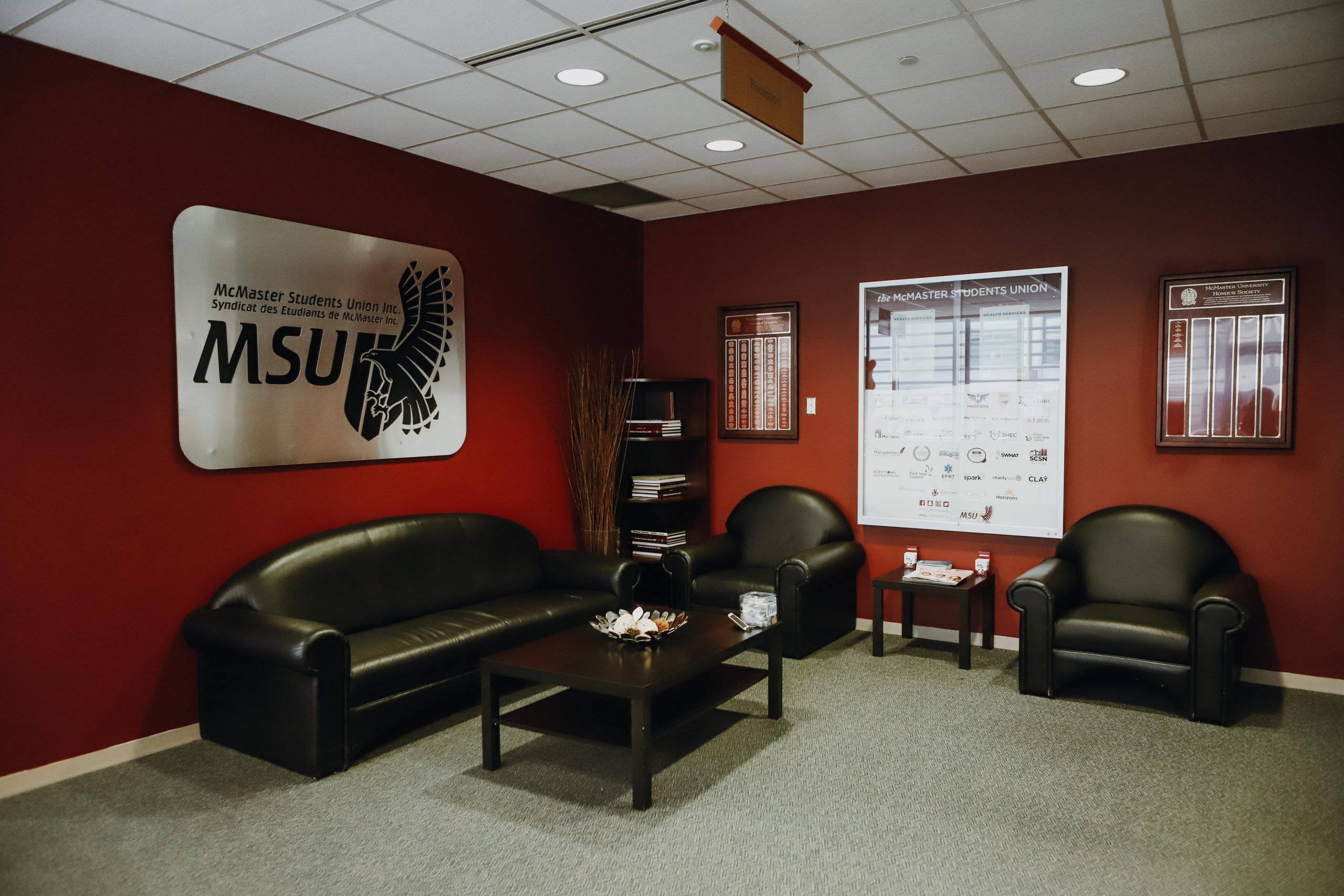 A picture of the MSU office with the MSU logo at the front. Underneath there is a black couch.