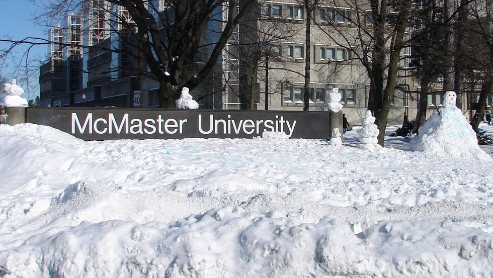 Photo of a McMaster sign and the campus covered in snow.