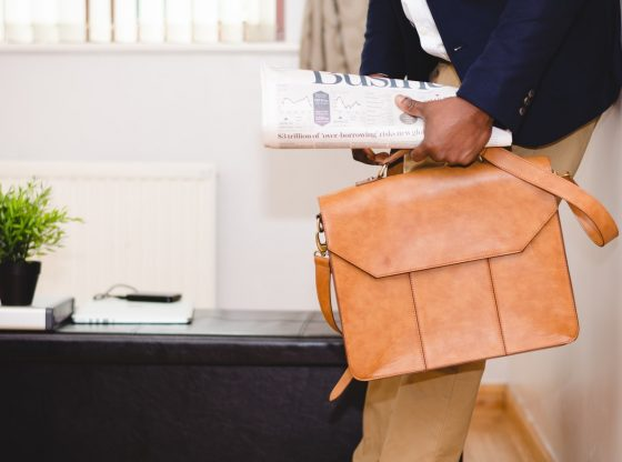 Picture of someone holding a briefcase, leaning against a wall.