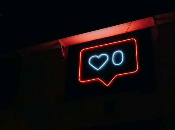 A fluorescent sign that has the likes symbol from Instagram.